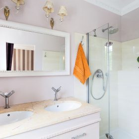 Vintage mansion - a bright rest room with a glass shower and stone sinks